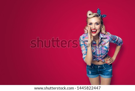 Beautiful happy excited woman holding hand near open mouth. Girl dressed in pin up. Blond model at retro fashion vintage concept, dark red color background. Copy space area for sign or text.