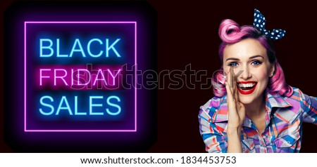 Beautiful happy excited woman holding hand near open mouth. Girl dressed in pin up. Blond model at retro fashion vintage advertising concept, over dark background. Black Friday sales neon light sign.  Foto stock ©