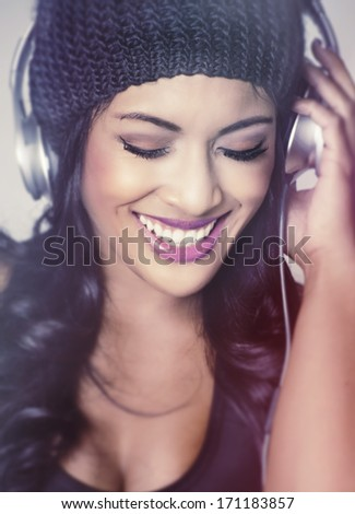 Beautiful happy excited young woman escaping to the sounds of the beat of music