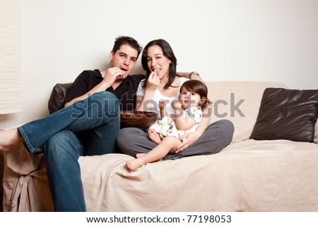 Beautiful happy family, father mother toddler daughter child, eating snacks while sitting on sofa couch in living room.