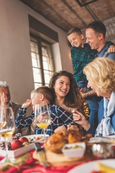 Beautiful happy family gathered around the table, having Christmas dinner, enjoying their time together and the winter holiday season