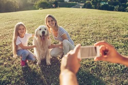 Beautiful happy family is having fun with golden retriever outdoors. Mother and daughter are sitting with dog labrador on green grass in park while father is making photo of them on a smart phone.
