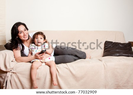 Beautiful happy family mother and baby toddler daughter sitting relaxed laid back on sofa couch in living room watching TV television.