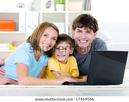 Beautiful happy family with little son relaxing at home with laptop - indoors