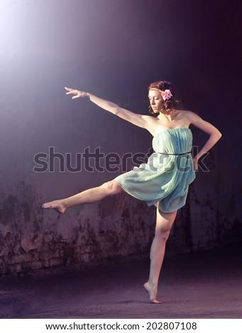 Beautiful happy girl dancing on dark grange background, toned