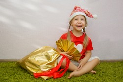 Beautiful happy girl in a Christmas santa claus hat with a bag of gifts sits on a green carpet in the room. The child rejoices and hugs a large Christmas bag with presents. Christmas and concept.