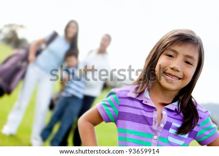 Beautiful happy girl with her family playing golf - stock photo