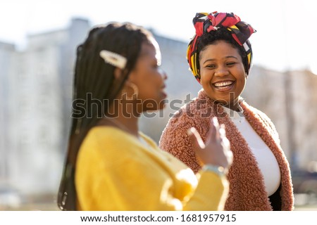 Beautiful happy girlfriends talking and smiling in city  Photo stock ©