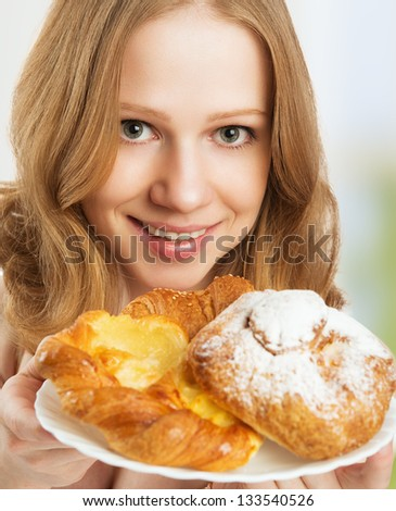 Beautiful happy healthy young woman offers treats cakes, scones, muffins, biscuits and buns