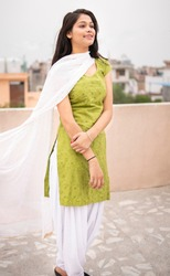Beautiful, happy Indian late teen girl enjoying fresh air in outdoor at day time. She is looking away and thinking with smile on her face. She is wearing traditional dress salwar Kameez and Dupatta.
