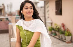 Beautiful happy Indian late teen girl listening music on smartphone through earphones and enjoying fresh air in outdoor on roof at day time. She is wearing traditional dress salwar Kameez and Dupatta.