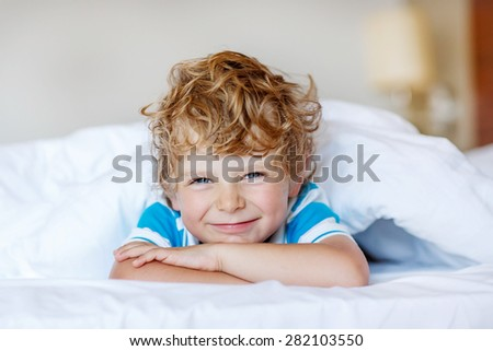 Beautiful happy kid boy after sleeping in his white bed. Little happy child smiling and laughing, indoors.