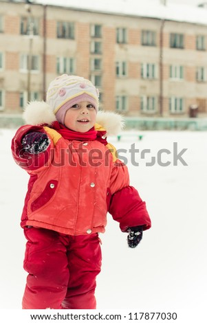 Beautiful happy kid in the red jacket hand points winter outdoors.