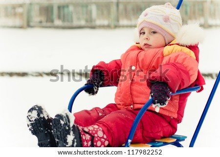 Beautiful happy kid in the red jacket on a sled winter outdoors.