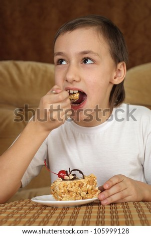 Beautiful happy lad sitting at a table on a brown background