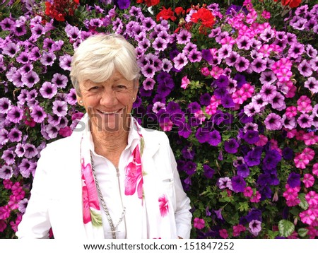 Beautiful happy lady in her seventies in front of petunia flowers.