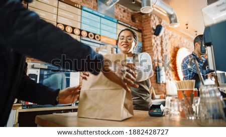 Beautiful Happy Latin Barista Serves Order to a Food Delivery Courier Picking Up Paper Bag with Pastries from a Cafe Restaurant. Delivery Guy Puts Food in His Hot Thermal Insulated Bag. Stock photo ©