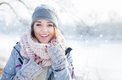 Beautiful  happy laughing young woman wearing winter hat gloves and scarf covered with snow flakes. Winter forest landscape background