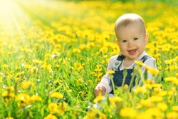 Beautiful happy little baby girl sitting on a green meadow with yellow flowers dandelions on the nature in the park