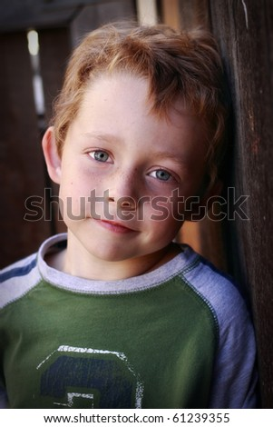 beautiful happy little boy leaning against a fence