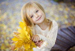 beautiful happy little girl has fun playing with fallen golden leaves in the autumn park