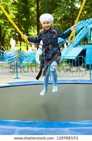 Beautiful happy little girl jumping on trampoline, against background of children's park.