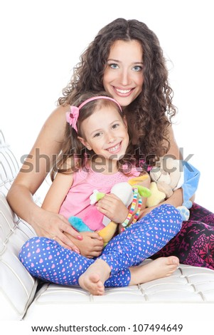 Beautiful happy mother and little daughter relaxing together on a sofa