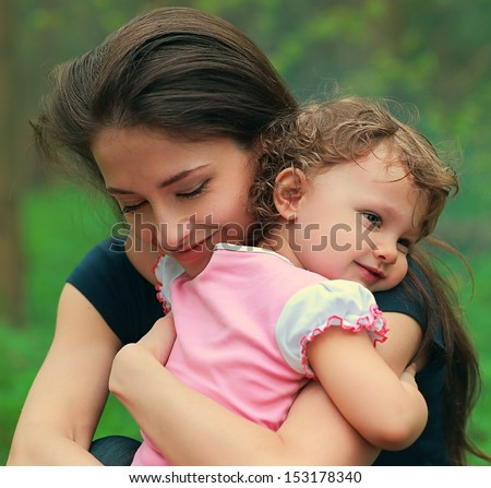 Beautiful happy mother hugging baby girl with love outdoors summer background. Closeup tender portrait
