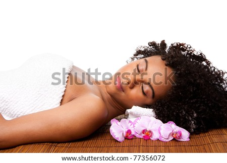 Beautiful happy peaceful sleeping Brazilian woman at a day spa, laying on bamboo massage table with head on pillow wearing a towel and orchid flowers around, isolated.