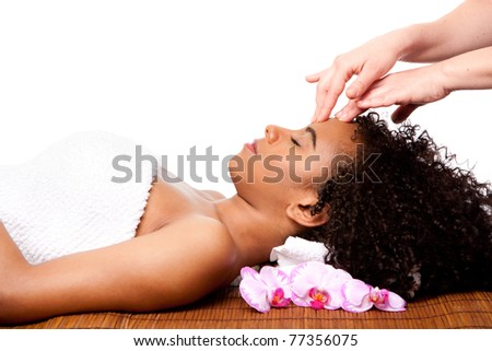 Beautiful happy peaceful sleeping Brazilian woman at day spa, laying on bamboo massage table with head on pillow wearing a towel getting a facial massage, isolated.