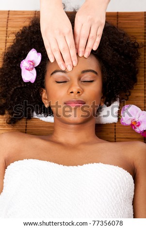Beautiful happy peaceful sleeping Brazilian woman at day spa, laying on bamboo massage table with head on pillow wearing a towel getting a facial massage.