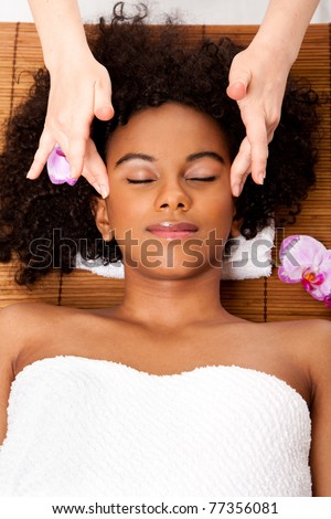 Beautiful happy peaceful sleeping Brazilian woman at day spa, laying on bamboo table with head on pillow wearing a towel getting a facial temple massage, isolated.