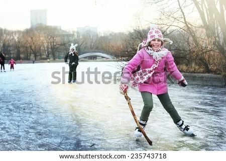 beautiful happy preteen girl figure skating in open winter ice skating rink