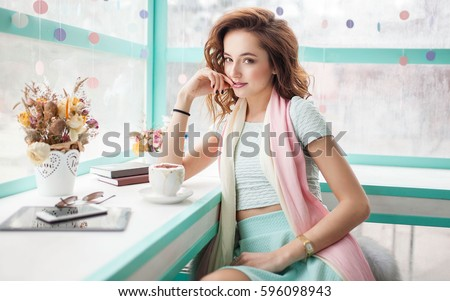 Beautiful happy pretty young woman sitting in a cafe with tablet and mobile phone. Spring trendy pink and blue colors. Flowers and books on the table. #596098943