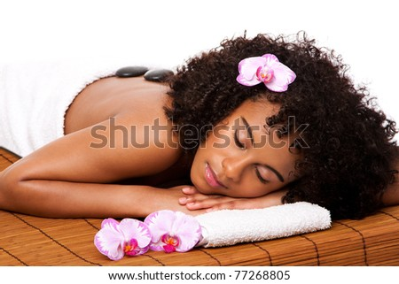 Beautiful happy relaxed Brazilian Latina-African woman at health day spa with hot stone massage treatment laying in white towel on bamboo table decorated with orchids.