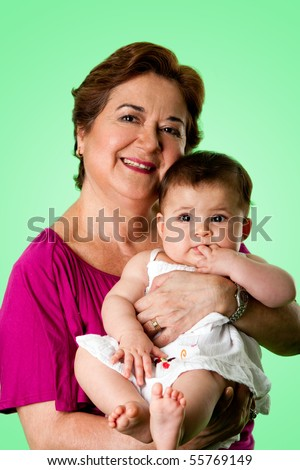 Beautiful happy senior Caucasian Hispanic Latina grandmother holding cute baby in arms, on a green background.