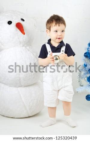 beautiful happy small kid decorate christmas tree