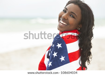 Beautiful happy smiling African American young woman or girl wrapped in American flag on a beach