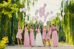Beautiful happy smiling bride with bridesmaids in light trendy pink dresses on walk outdoors holding pink balloons in green summer city park. Friends, maid of honor, female friendship, wedding concept