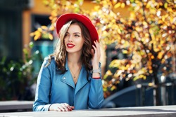 Beautiful happy smiling girl with long hair, red lips, wearing stylish hat, blue jacket posing in autumn street. Outdoor portrait, day light. Female autumn fashion concept. Copy, empty space for text