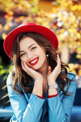 Beautiful happy smiling girl with long hair, red lips, wearing stylish hat, blue jacket posing in autumn street. Close up outdoor portrait.  Female fashion concept