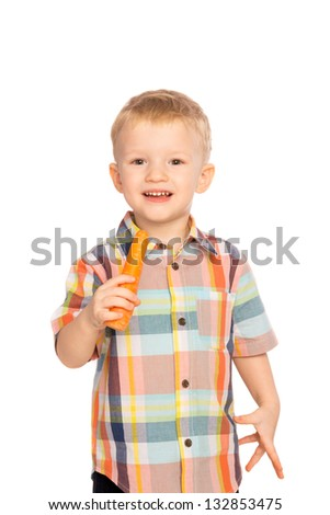 Beautiful happy smiling joyful child (little boy) eating healthy food (vegetable, carrot) isolated on white background