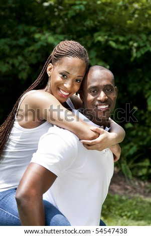 Beautiful happy smiling laughing young African American couple piggyback playing in the park, woman hugging man, wearing white shirts and blue jeans.