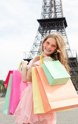 Beautiful happy smiling little girl child in sunglasses are holding shopping bags outdoors and Eiffel Tower in background.. Lifestyle concept