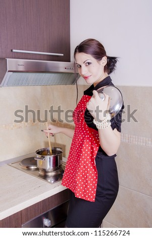 Beautiful happy smiling woman in the kitchen interior cooking