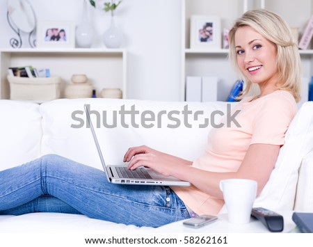 Beautiful happy smiling woman lying on the sofa with laptop - stock photo