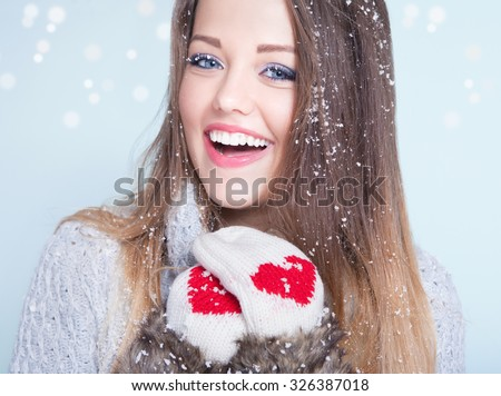 Beautiful happy smiling young woman wearing winter gloves covered with snow flakes. Christmas portrait concept.