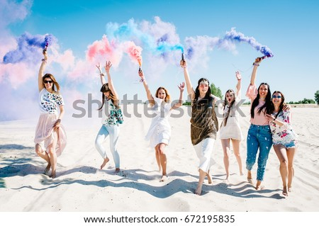 Shutterstock Beautiful happy stylish sexy young girls stand beach and hold light up colored smoke bombs. burn up. Sincere smiles. Party in Style boho. Maiden evening Hen-parties. Bachelorette. Close up. Portrait