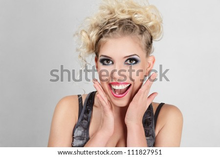 Beautiful happy surprised blonde young woman studio portrait