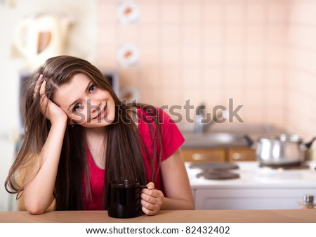 beautiful happy teen girl drinking coffee at home